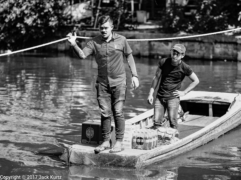 16 FEBRUARY 2017 - THEPHARAK, SAMUT PRAKAN, THAILAND: A boatman takes a passenger and his cargo across Khlong Samrong in his small boat, which he uses as a ferry, in the Bangkok suburbs. The boatman pulls it across using a system of ropes and pulleys. He's been working on the boat since he was a child. Small ferries like this used to be common in Bangkok but many of the khlongs (the canals that used to crisscross Bangkok) have been filled in and bridges have been across the remaining khlongs. Now there are only a handful of the ferries left. This ferry charges 2 Baht (the equivalent of about .06¢ US) per person to take a person across the khlong.      PHOTO BY JACK KURTZ