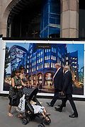 Pedestrians and a construction hoarding for the Minster Building, on 14th August 2017, in the City of London, England.