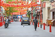 A food delivery worker is seen looking for the Chinese food supply shop to pick up his next job in deserted China Town in London, Britain, on Sunday, May 3, 2020. (Photo/ Vudi Xhymshiti)