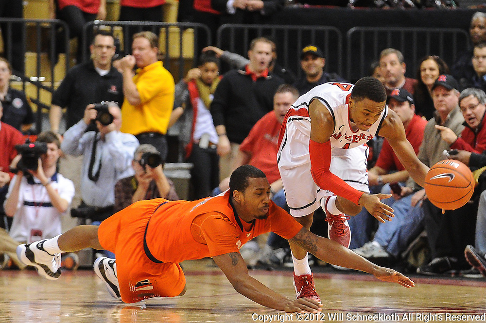 Rutgers Scarlet Knights guard Myles Mack (4) grabs a loose ball away from diving Syracuse Orange forward Kris Joseph (32) during second half NCAA Big East basketball action between #2 Syracuse and Rutgers at the Louis Brown Athletic Center. Syracuse defeated Rutgers 74-64.