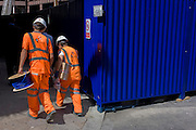 Workmen in hi-visibility clothing carry a blue wiring reel, coincidentally the same colour as a construction container.