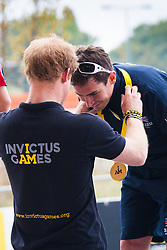 Queen Elizabeth Olympic Park, London. September 13th 2014. Prince Harry awards IRB2 cyclist Jaco Van Gass of Great Britain his gold medal as wounded servicemen and women from 13 different countries compete for sporting glory during the cycling competition at the Invictus Games.