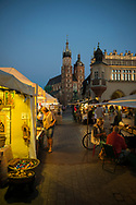 People on a late summer evening in Rynek Glowny Square in the heart of Krakow, Poland. In the background is the 262-foot tall Church of Our Lady Assumed into Heaven, also called St. Mary's Church, a Gothic church re-built in the 14th century.