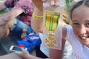 Nederland, Nijmegen, 21-7-2017 Intocht van de wandelaars in Nijmegen op de vierde dag van de 101e 4Daagse . Het vierdaagselegioen loopt over de Via Gladiola Nijmegen binnen. vlak voor de deadline van 18.00 uur komen nog mensen aan op de Wedren, uitgeput maar blij. Na een feestelijke intocht volgt de uiteindelijke finish en het ophalen van het kruisje, vierdaagsekruisje, medaille, op de Wedren. Iedere deelnemer krijgt een bloem, gladiool, uitgerijkt. Foto: Flip Franssen