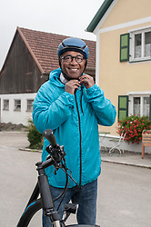 Senior man fastening on bicycle helmet and smiling, Bavaria, Germany