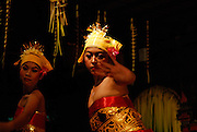 Two young women performing a traditional Balinese Legong dance, tari Tenun. Sanur, Bali, Indonesia