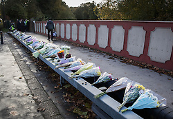 © Licensed to London News Pictures. 13/11/2016. Croydon, UK. Floral tributes are placed a bridge overlooking the tramline. Engineers work to restore the line at the site where seven people died and 50 were injured when a tram rolled over on Wednesday 9th November. Photo credit: Peter Macdiarmid/LNP