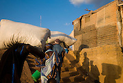Men unloading  boat in Mopti's harbour. At the confluence of the Niger and the Bani rivers, between Timbuktu and SÈgou, Mopti is the second largest city in Mali, and the hub for commerce and tourism in this west-african landlocked country.