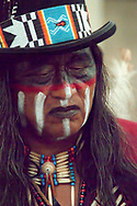 Indian in a top hat with a bold colorful beaded band. Black blindfold face paint and black lipstick, long salt and pepper hair dressed for a powwow.