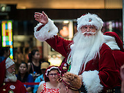 17 SEPTEMBER 2015 - BANGKOK, THAILAND:  A Santa Claus waves to the crowd during the World Santa Claus Congress in Bangkok. Twenty-six Santa Clauses from around the world are in Bangkok for the first World Santa Claus Congress. The World Santa Claus Congress has been an annual event in Denmark since 1957. This year's event, hosted by Snow Town, a theme park with a winter and snow theme, hosted the event. There were Santas from Japan, Hong Kong, the US, Canada, Germany, France and Denmark. They presented gifts to Thai children and judged a Santa pageant. Thailand, a Buddhist country, does not celebrate the religious aspects of Christmas, but Thais do celebrate the commercial aspects of the holiday.   PHOTO BY JACK KURTZ