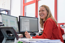 Woman working in office and smiling, Munich, Bavaria, Germany