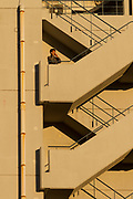A Japanese office worker or salaryman smokes and speaks on a cellphone on the outside stairs of a tall building in Shinjuku, Tokyo, Japan. Tuesday November 29th 2016