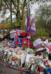 © Licensed to London News Pictures. 13/11/2016. Croydon, UK. Flags, flowers and other tributes to the victims of the Croydon tram crash are laid out near Sandilands station. Engineers are working to restore the line at the site where seven people died and 50 were injured when a tram rolled over on Wednesday 9th November. Photo credit: Peter Macdiarmid/LNP