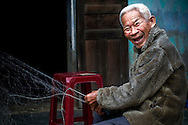Portrait of an old Vietnamese fisherman laughing as he looks towards the camera while repairing his fishing net, Tam Hai, Vietnam, Southeast Asia