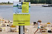 Nederland, The Netherlands, Nijmegen, 19-8-2018Op een strandje langs de waal is een waarschuwing oipgehangen door rws, rijkswaterstaat, om met de lage stand van de waal niet in de rivier te zwemmen .Foto: Flip Franssen