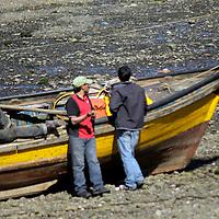 South America, Chile, Puerto Montt. Fishermen on boat in Puerto Montt harbor.