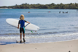 Rear view of girl with surfboard at beach, Mauritius