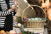 Florist arranges a flower bouquet in a basket