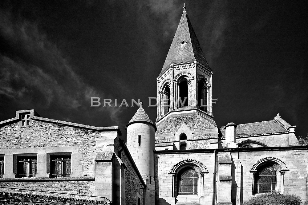 Stunning contrast highlighting architecture of Saint Martin Church in Louveciennes, France against a deep indigo sky.  Aspect Ratio 1w x 0.667h.