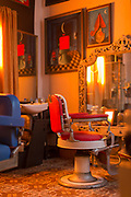 Inside hair saloon with red and blue chair and window, Havana, Cuba