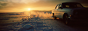 Car driving alond an ice road on the frozen Lake Baikal, Siberia, Russia
