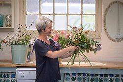 Rachel Siegfried making a hand tied  flower arrangement. Checking in a mirror.
