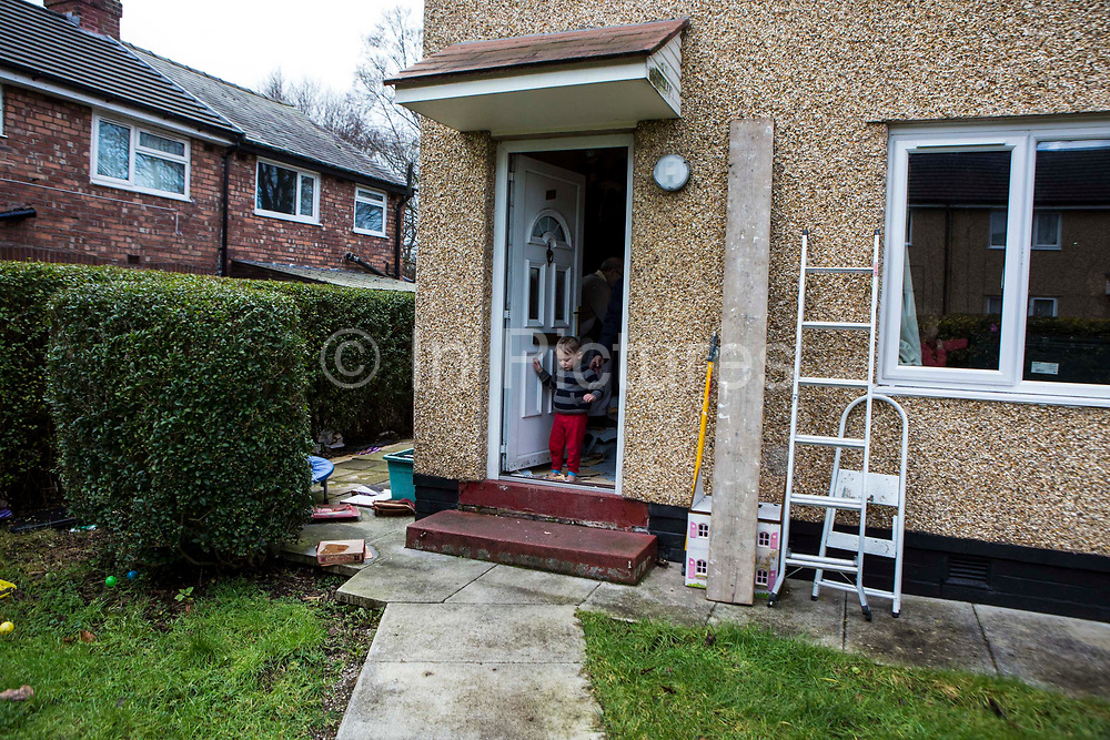 Children playing on the front doorstep of their family home. Leyland, Lancashire.