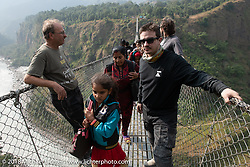 Kiwi Mike Tomas and Chris Shelby on the Kusma Gyadi Bridge, the tallest (443') and one of the longest (1,128') suspension bridges in the country, on Day-7 of our Himalayan Heroes adventure riding from Tatopani to Pokhara, Nepal. Monday, November 12, 2018. Photography ©2018 Michael Lichter.