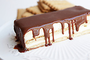 biscuit layer cream cake topped with chocolate. Base and layers are made from biscuits (seen in the background)