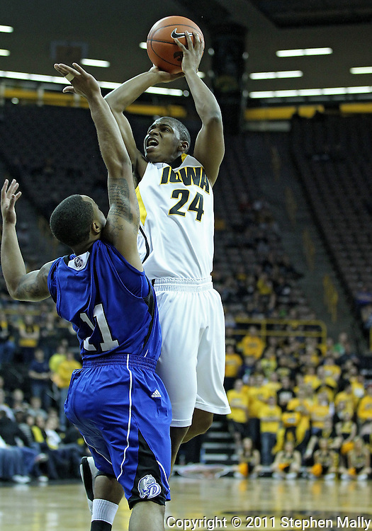 December 17, 2011: Iowa Hawkeyes guard Bryce Cartwright (24) puts up a shot over Drake Bulldogs guard Karl Madison (11) during the the NCAA basketball game between the Drake Bulldogs and the Iowa Hawkeyes at Carver-Hawkeye Arena in Iowa City, Iowa on Saturday, December 17, 2011. Iowa defeated Drake 82-68.