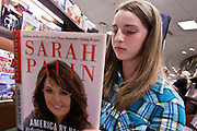 """23 NOVEMBER 2010 - PHOENIX, AZ:  TAMARA STATMAN, 13, from Phoenix, AZ, reads Sarah Palin's new book, """"America by Heart"""" while waiting to get the book signed at a Barnes and Noble in Phoenix Tuesday. Statman, described herself as a political junkie and said she admires Palin and plans to run for president herself in 2044. Palin signed copies of her new book, """"America by Heart"""" at the store in north Phoenix Tuesday night, Nov. 23. It was the kick off of her book tour to support America by Heart. Palin is frequently mentioned as a possible Republican candidate for US President in 2012.   Photo by Jack Kurtz"""