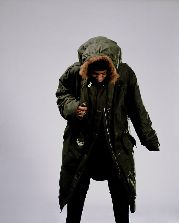 Woman in a green hooded coat looking down.