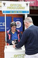 AFC Wimbledon programme seller in front of EFL sign for family excellence during the EFL Sky Bet League 1 match between AFC Wimbledon and Rochdale at the Cherry Red Records Stadium, Kingston, England on 5 October 2019.