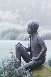 Frozen statue - 'Boy on a Rock' by Jane Hogben in John Massey's garden on a frosty winter's morning