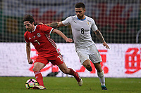 """Joe Allen, left, of Wales national football team kicks the ball to make a pass against Nahitan Nandez of Uruguay national football team in their final match during the 2018 Gree China Cup International Football Championship in Nanning city, south China's Guangxi Zhuang Autonomous Region, 26 March 2018.<br /> <br /> Edinson Cavani's goal in the second half helped Uruguay beat Wales to claim the title of the second edition of China Cup International Football Championship here on Monday (26 March 2018). """"It was a tough match. I'm very satisfied with the result and I think that we can even get better if we didn't suffer from jet lag or injuries. I think the result was very satisfactory,"""" said Uruguay coach Oscar Tabarez. Wales were buoyed by a 6-0 victory over China while Uruguay were fresh from a 2-0 win over the Czech Republic. Uruguay almost took a dream start just 3 minutes into the game as Luis Suarez's shot on Nahitan Nandez cross smacked the upright. Uruguay were dealt a blow on 8 minutes when Jose Gimenez was injured in a challenge and was replaced by Sebastian Coates. Inter Milan's midfielder Matias Vecino of Uruguay also fired at the edge of box from a looped pass but only saw his attempt whistle past the post. Suarez squandered a golden opportunity on 32 minutes when Ashley Williams's wayward backpass sent him clear, but the Barca hitman rattled the woodwork again with goalkeeper Wayne Hennessey well beaten."""