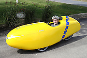 A velomobile or bicycle car is a human-powered vehicle, enclosed for protection from weather and collisions.  Here a young man is peddling the velomobile in a recumbent position.  The velomobile is built on a recumbent bike frame with two steerable wheels in the front and one wheel in the back.  This tricycle design allows for a stable vehicle on wet roads.  The vehicle is air streamed to decrease wind resistance and shield the rider from rain.  As fuel consumption becomes more of an issue, more commuters will switch to human powered vehicles.