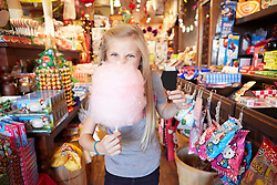 Lifestyle image of girl eating candy floss in candy store