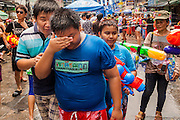 13 APRIL 2014 - BANGKOK, THAILAND: Thai children walk through a water fight on Khao San Road in Bangkok. Songkran is celebrated in Thailand as the traditional New Year's Day from 13 to 16 April. Songkran is in the hottest time of the year in Thailand, at the end of the dry season and provides an excuse for people to cool off in friendly water fights that take place throughout the country. Songkran has been a national holiday since 1940, when Thailand moved the first day of the year to January 1.    PHOTO BY JACK KURTZ