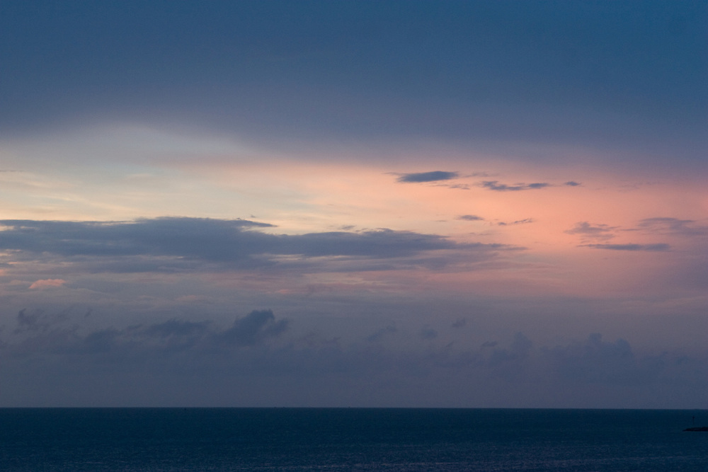 Sunset over the ocean with dark, looming clouds.