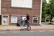 Een man rijdt op een zelf gebouwde hoge fiets door Utrecht.<br /> <br /> A man rides a very special homemade bicycle in Utrecht.