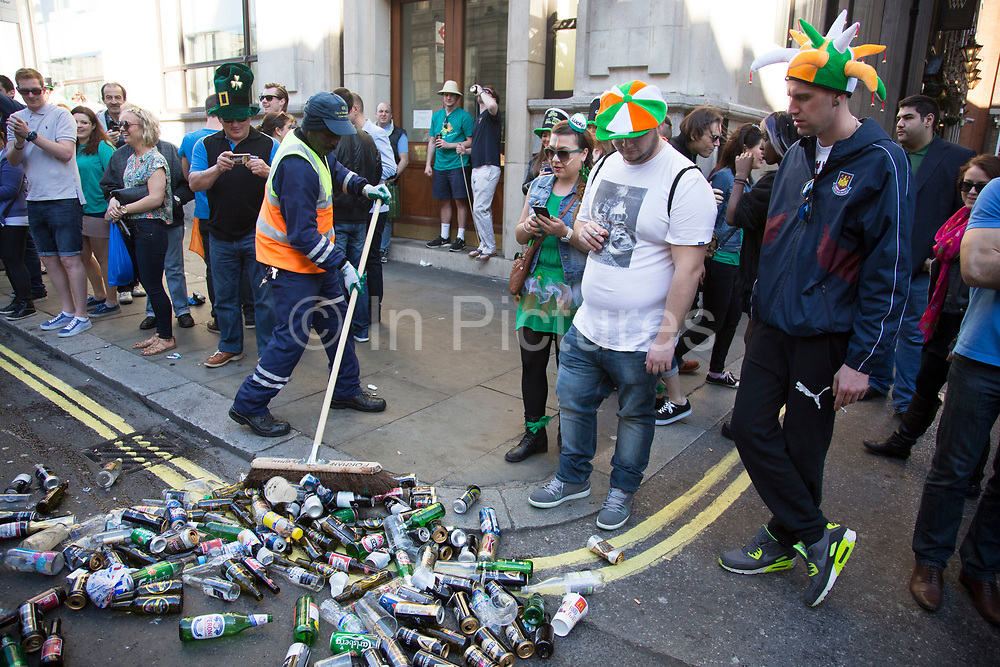 London, UK. Sunday 16th March 2014. Revellers gather in central London for the annual St Patrick's Day celebrations. Saint Patrick's Day or the Feast of Saint Patrick is a cultural and religious holiday celebrated annually on 17 March, the death date of the most commonly-recognised patron saint of Ireland, Saint Patrick. Nowadays the celebration is a fun excuse for some craic and lots of drinking. Council workers clearing up the empty bottles and cans of alcohol.