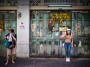 """26 FEBRUARY 2019 - BANGKOK, THAILAND: A woman poses for photos against a weathered wall in Bangkok's Chinatown. Bangkok has one of the largest """"Chinatown"""" districts in the world. About 14% of all Thais have some Chinese ancestry and Chinese cultural practices are incorporated in many facets of Thai daily life.       PHOTO BY JACK KURTZ"""