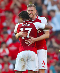 Arsenal's Alex Iwobi (left) and Arsenal's Per Mertesacker celebrate after the final whistle