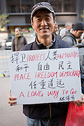 "An Asian man holds a sign reading, in English, ""Protect humanity's peace freedom democracy a long way to go."""