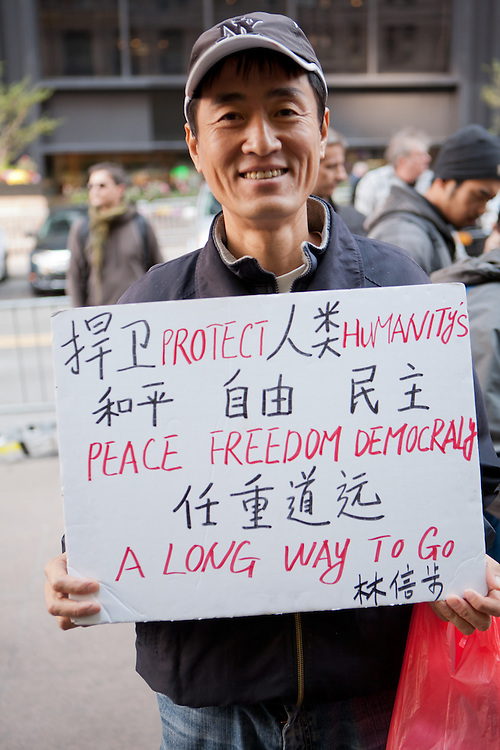 """An Asian man holds a sign reading, in English, """"Protect humanity's peace freedom democracy a long way to go."""""""