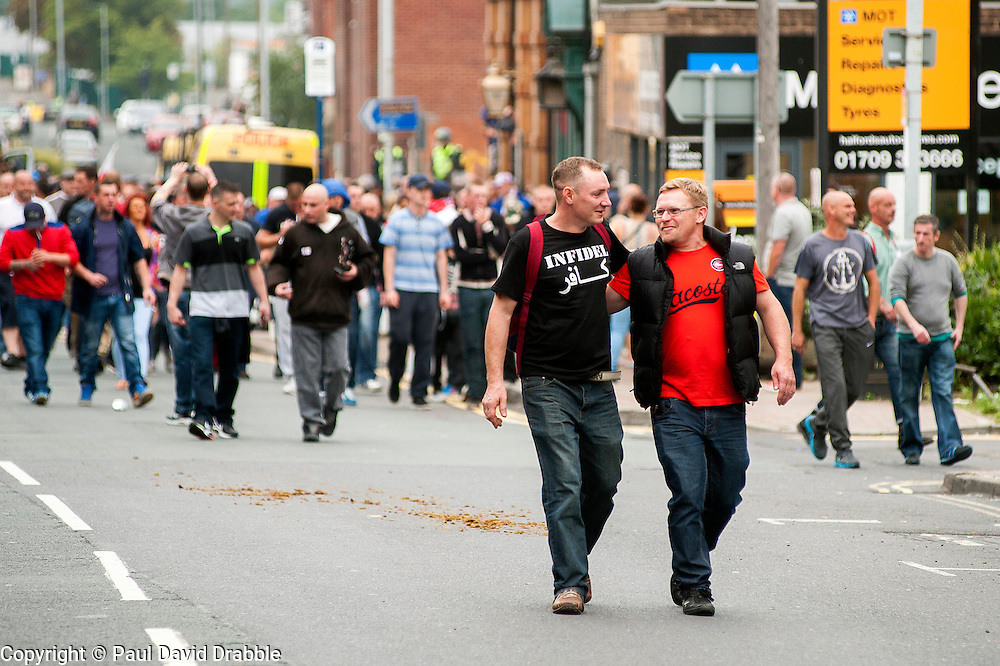 """Rotherham England<br /> 13 September 2014 <br /> EDL members and Supporters make their way back onto the official route after the EDL broke through a police cordon during the English Defence League Justice for the Rotherham 1400 March described by an EDL Facebook Page as """"a protest against the Pakistani Muslim grooming gangs"""" on Saturday Afternoon <br /> <br /> <br /> Image © Paul David Drabble <br /> www.pauldaviddrabble.co.uk"""