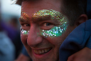 Glastonbury Festival, 2015.<br /> Man smiling with glitter face paint