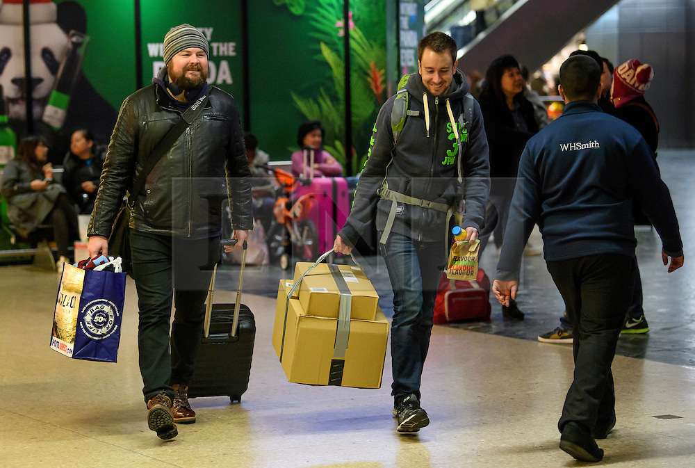 © Licensed to London News Pictures. 24/12/2016. London, UK. Festive holiday makers carrying gifts as they board a train at Euston Station in London on Christmas Eve, as the Christmas getaway continues, with stations, airports and roads expected to be very busy as people start their Christmas holidays. Photo credit: Ben Cawthra/LNP