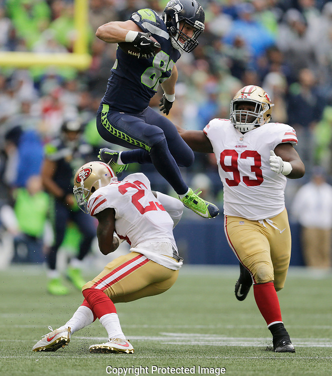 Seattle Seahawks tight end Luke Willson leaps over San Francisco 49ers cornerback Will Redmond, left, as defensive tackle D.J. Jones (93) looks on in the first half of an NFL football game, Sunday, Sept. 17, 2017, in Seattle. (AP Photo/John Froschauer)