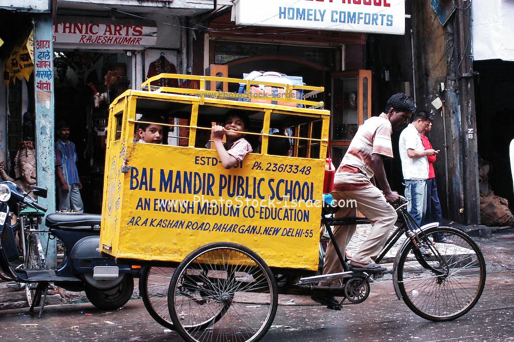 Delhi, India, the main bazaar street, school transportation a bicycle rickshaw